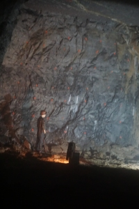 An example of a man next to the cavern wall.