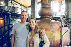 Lindsey & Jerod pose in front of the copper pot still.